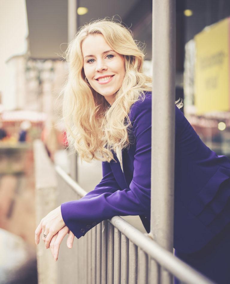 Constanze Bloeck blickt lächelnd in Kamera und lehnt dabei über ein Geländer